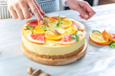 Raw citrus cake with grapefruit, orange, lime and lemon with nuts and mint. Healthy fresh summer dessert