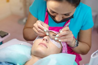 Woman master in the beauty salon is working on eyelash extension to the client. Process of working as a professional stylist for lengthening eyelashes