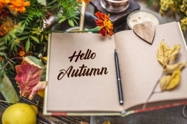 Autumn set of yellow leaves and flowers. Notebook with open pages on the table. Top view. Concept Hello autumn