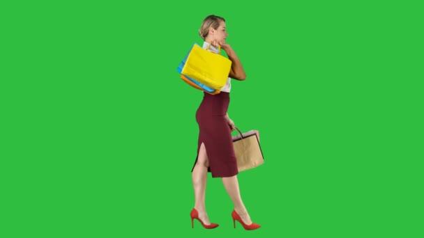Přejeme vám příjemné nakupování. Womanholding vícebarevný, nákupní tašky a chůzi na zelené obrazovce, Chroma Key.