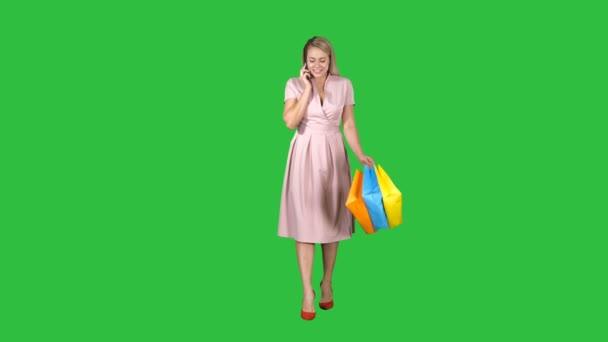 junge Frau beim Einkaufen und Telefonieren auf einem grünen Bildschirm, Chroma-Schlüssel.