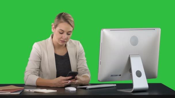 Nő mobiltelefon használata a pultnál egy zöld képernyő Chroma Key.