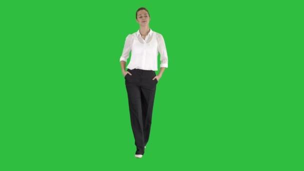 Celou délku zastřelil. Glamour obchodních žena chodí s rukama v kapsách na zelené obrazovce, klíčování Chroma. Profesionální snímek v rozlišení 4 k. 009. můžete použít ji například ve sportu, jóga, zdravá