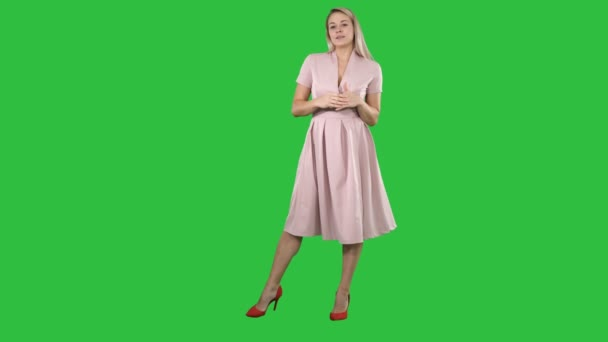 Happy blonde woman in pink talking to camera and pointing to the side on a Green Screen, Chroma Key.