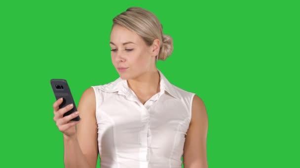 junges Mädchen liest von Handy-Bildschirm auf grünem Bildschirm, Chroma-Schlüssel.