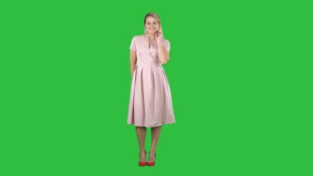 Nádherná mladá žena v letních šatech pózuje s plachý úsměv na zelené obrazovce, Chroma Key.