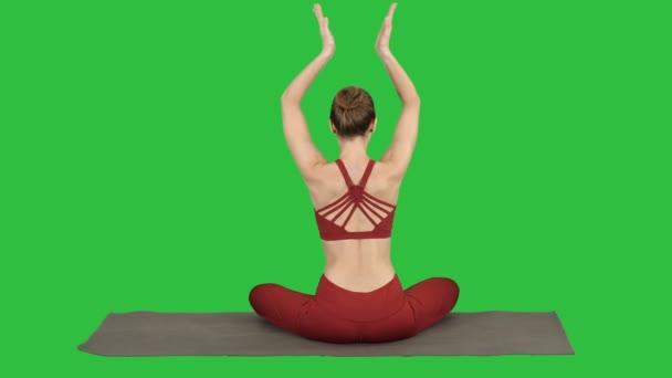 junge sportliche Frau sitzt in Lotus-Pose, die Hände über dem Kopf auf einem grünen Bildschirm, Chroma-Schlüssel.