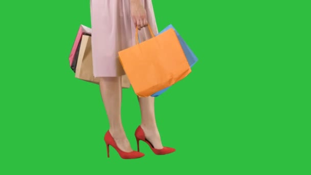 Teil Körper, schöne weibliche schlanke Beine sexy Mädchen hält ein Papier Einkaufstüten auf einem grünen Bildschirm, Chroma-Schlüssel.