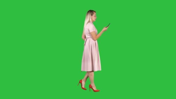 Frau in rosa Kleid telefoniert auf grünem Bildschirm, Chroma-Schlüssel.