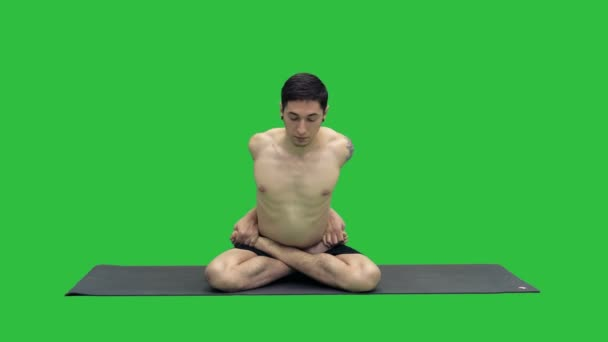 Young man practicing yoga in lotus position on a Green Screen, Chroma Key.