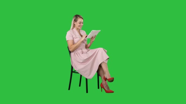 Funny pretty young woman in pink dress sitting on a chair and using tablet on a Green Screen, Chroma Key.