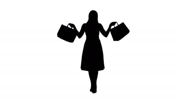 Silueta Mladé blondýny dívka v růžových šatech ukazuje na kameru nákupní tašky a chůzi.
