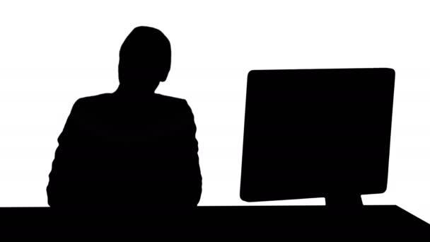 Sziluettjét vidám üzletasszony ül az asztalnál, az office, és látszó-on fényképezőgép Professional lövés 4 k felbontású. 007. használhatja például az a videó, üzleti, bemutató
