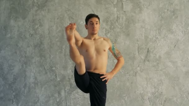 Male yoga master stretching leg in the studio. Standing, holding one leg in the hand.