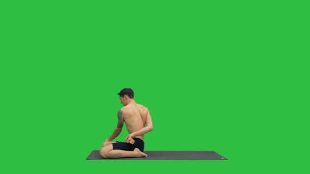 Mladý silný muž dělá cvičení jógy roztáhne nohy padmasana na zelené obrazovce, Chroma Key.