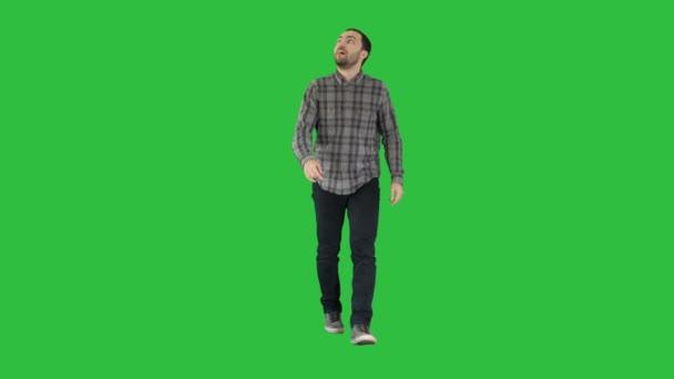 junger Mann, der fasziniert auf einen grünen Bildschirm blickt, Chroma-Schlüssel.