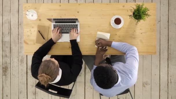 Dva kolegové diskutují o datech na notebooku a zapisují poznámky