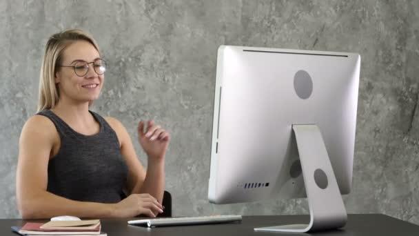 Geschäftsfrau im Büro mit Videokonferenz am Computer.