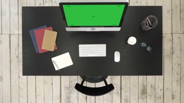 Büroschreibtisch mit Computer und Bildschirm, Kamera gesehen. Green-Screen-Mock-up-Display.