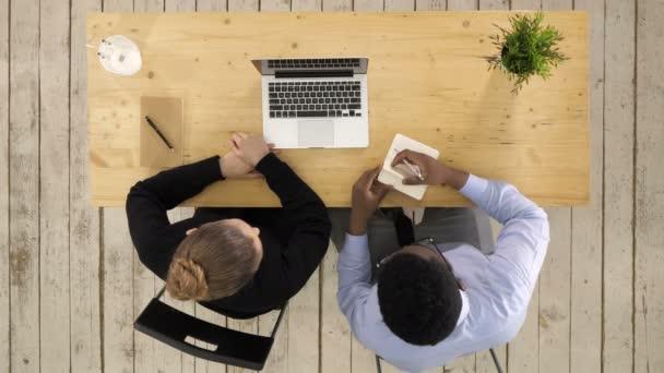 Zwei Unternehmer sitzen zusammen in einem Schreibtisch Notebook Noten gesetzt