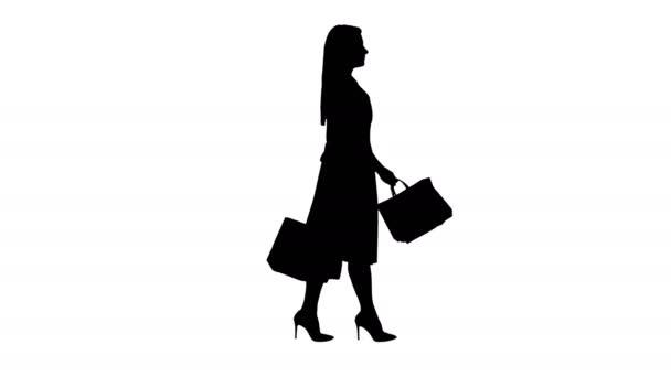 Silueta Mladá žena s nákupními taškami při pohledu na displej okna