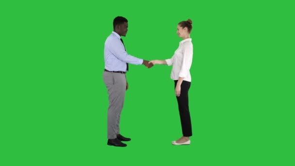 Handshake of business woman and business man posing for the picture on a Green Screen, Chroma Key.