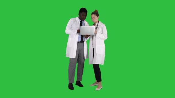 Zdravotnický personál pracující před šedý notebook stoje na zelené obrazovce, Chroma Key.