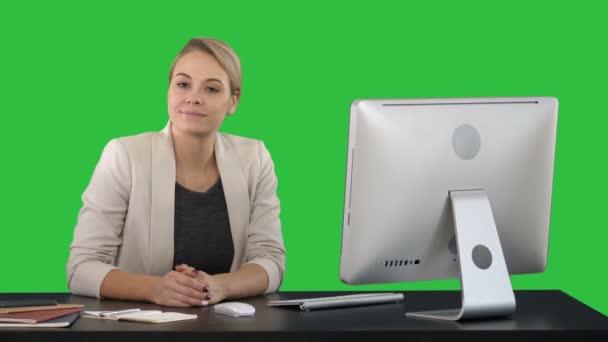 Vidám üzletasszony ül az asztalnál, az office, és látszó-nél fényképezőgép egy zöld képernyő, Chroma Key.