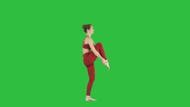 Fiatal jógi nő gyakorló jóga koncepció változása a Utthita Hasta Padangushthasana jelent, Trivikramasana, állandó osztja a egy zöld képernyő Chroma Key.