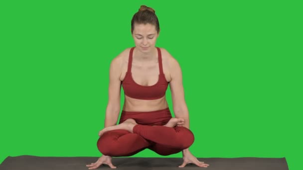 Beautiful young woman doing yoga or pilates exercise Arm balance with crossed legs, Scale Posture, Tolasana, Utpluthi on a Green Screen, Chroma Key.
