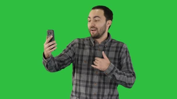 Junge Blogger Aufzeichnung auf seinem Handy video während des Gehens auf einem Green-Screen, Chroma-Key.