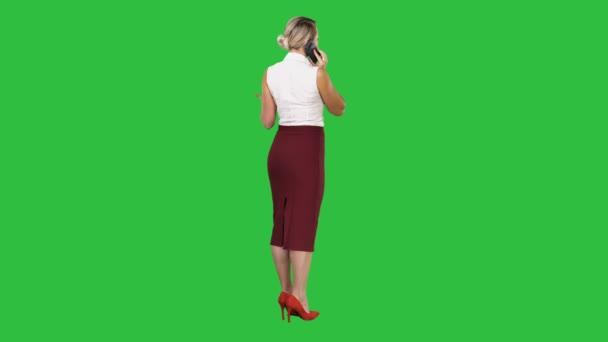 stehend junge schöne Frau mit einem Mobiltelefon, das einen Anruf auf einem grünen Bildschirm, Chroma-Schlüssel.