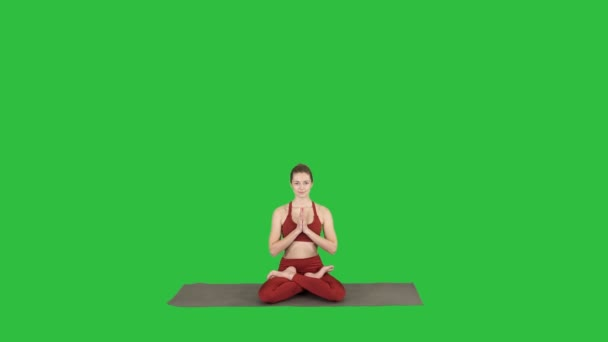 Young sporty woman practicing yoga, doing Scale exercise, Tolasana pose on a Green Screen, Chroma Key.