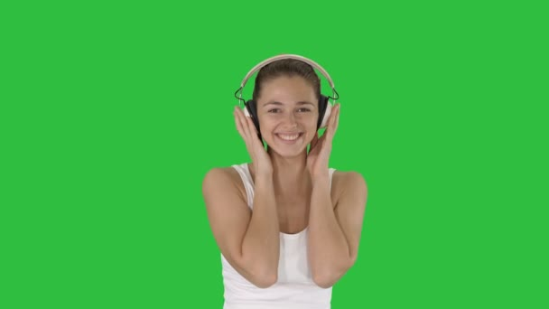 Woman with headphones listening music and making funny face on a Green Screen, Chroma Key.