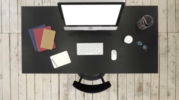 Bürotisch mit Computer und Bildschirm vor der Kamera. Weißes Display.