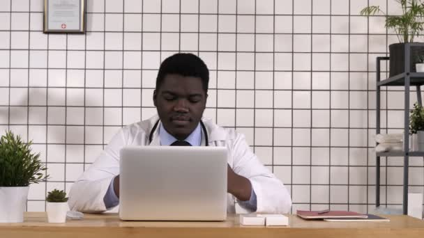 Doctor looking at new tablets and checking info on laptop.