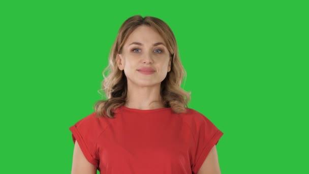 junge kaukasische Frau zeigt mit der Hand und dem Finger zur Seite auf einen grünen Bildschirm, Chroma-Taste.