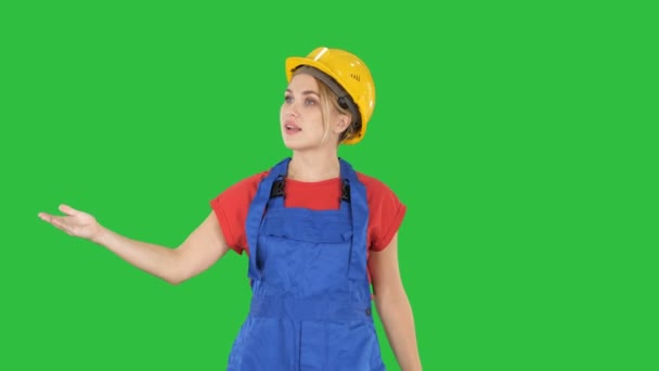 Young smiling worker woman talking and showing objects to her sides on a Green Screen, Chroma Key.