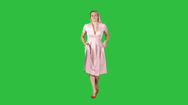 Žena v růžových šatech s rukama v kapsách kráčí směrem k fotoaparátu na zelené obrazovce, Chroma Key.
