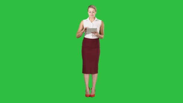 Happy young lady standing using tablet and looking to the camera on a Green Screen, Chroma Key.