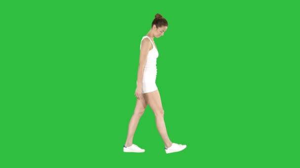 Po celé délce boční pohled. Mladá žena v sportovní procházce shlížel na zelené obrazovce, klíčování Chroma. Profesionální snímek v rozlišení 4 k. 009. můžete použít ji například ve sportu, jóga, zdravá