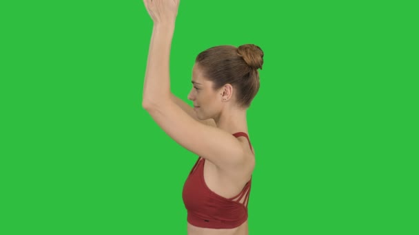 Young woman practicing yoga on a Green Screen, Chroma Key.