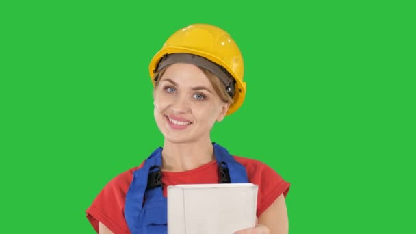 Young construction worker with tablet computer presenting something on a Green Screen, Chroma Key.