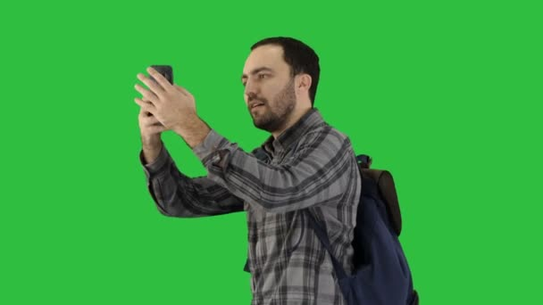 Handsome young man carrying backpack and taking a picture of himself on a Green Screen, Chroma Key.