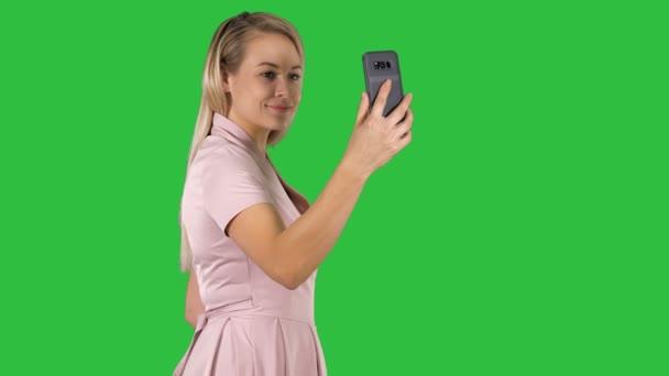junge schöne Frau macht Selfie auf ihrem Handy auf einem grünen Bildschirm, Chroma-Schlüssel.