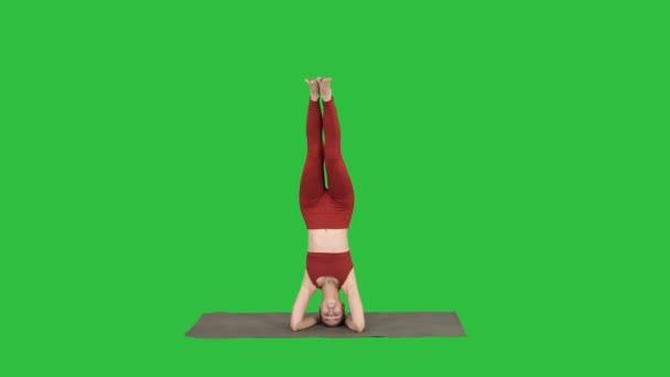 Schuss in voller Länge. schöne junge Frau macht Yoga-Übung Variation der unterstützten Kopfstand, garuda salamba sirsasana mit überkreuzten Beinen auf einem grünen Bildschirm, Chroma-Taste. Profi-Schuss in 4k
