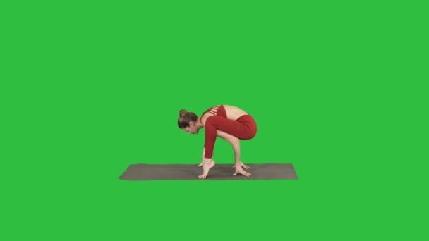 Beautiful woman practices handstand yoga asana Tittibhasana - firefly pose on a Green Screen, Chroma Key.