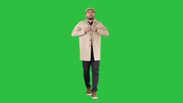 Mladý pohledný muž chodí a tlačítka nahoru plášť na zelené obrazovce, Chroma Key