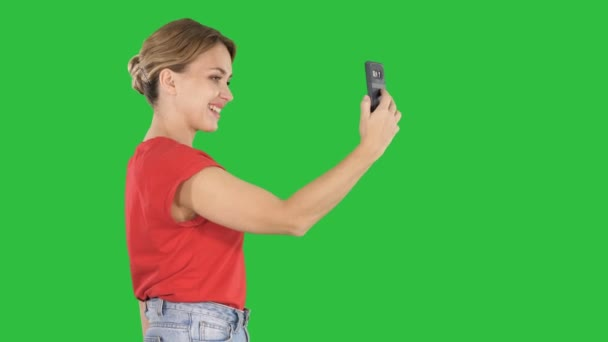 Beautiful young woman walking and holding a smartphone up to take pictures and selfies on a Green Screen, Chroma Key.
