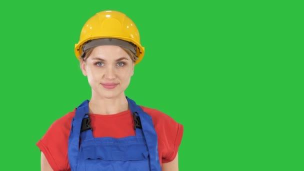 lächelnde Bauarbeiterin im Stehen und in wechselnden Posen gefaltete Hände, Hände auf den Hüften, Hände in Taschen auf einem grünen Bildschirm, Chroma-Schlüssel.